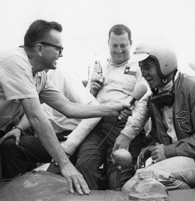 In typical fashion, Economaki interviews Roger Penske, winner of the Nassau Trophy race on Dec. 6, 1964, as teammate Hap Sharp looks on. [Image from IMRRC's National Speed Sport News Collection]