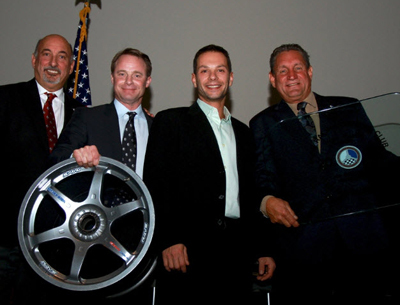 Lawrence Loshak (third from left) poses with the presenters of the Mark Donohue Award. That's Bobby Rahl on the far left, next to Donohue's son David Donohue holding the wheel that forms the base of the trophy. Dorsey Schroeder (far right) holds the engraved glass table top. [Brian Cleary image]